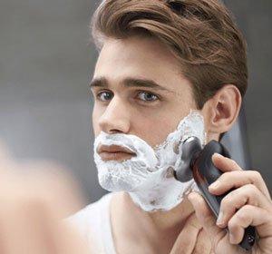 radersi con la schiuma da barba e un rasoio elettrico